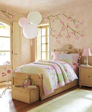 Flowers on the walls, hanging paper balls, Swedish style headboard. From Pottery Barn Kids