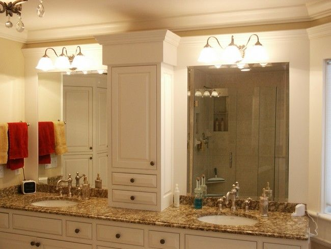 White lighting above twin mirrors separated by a cabinet in the middle