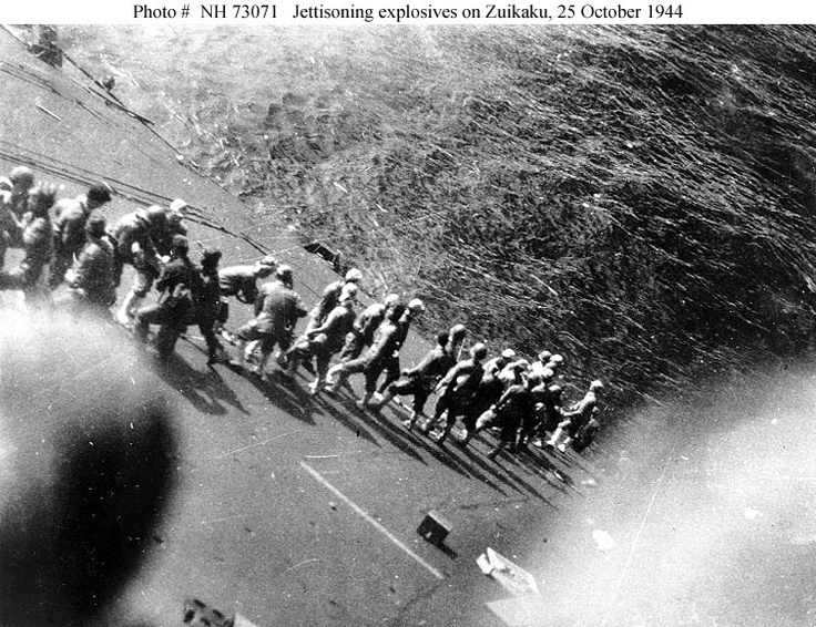 Battle off Cape Engano, 25 October 1944. Crewmembers of the listing Japanese aircraft carrier Zuikaku, Zuikaku, last of the six carriers that started the Pacific War with the Pearl Harbor attack almost three years earlier,  throwing explosives over the side, after she had been damaged by U.S. carrier aircraft on 25 October. Photographed from the carrier's island, looking to port. Courtesy of Mr. Kazutoshi Hando, 1970.