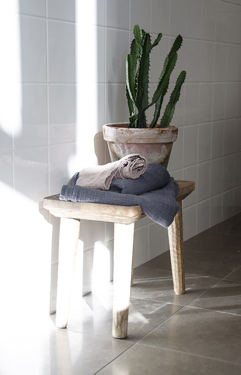 Handy styling opportunity plus towel storage - and a hand-made wooden stool softens the hard surfaces.