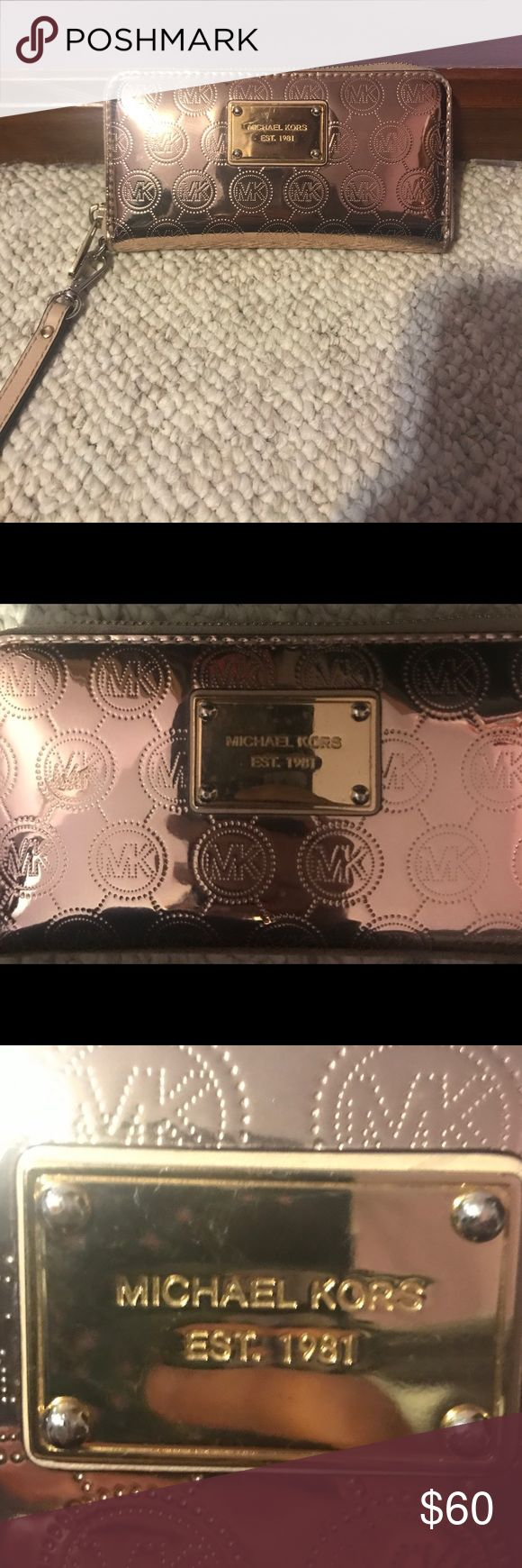 Micheal Kors Rose Gold Wallet Rose gold, MK logo wallet. In good condition, with some scratches on the metal logo (pictured) and a small pen mark by the zipper (also pictured). About 2 year's old, and includes: a money slot, space for a phone, zippered coin pouch, and 3 credit card holding spots inside. Michael Kors Bags Wallets