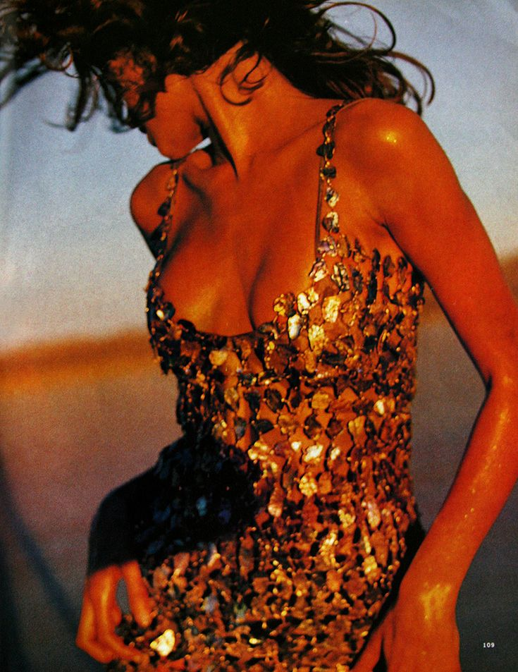 Stephanie Seymour by Sante D'Orazio, 1991: Timeless gold sparkle and a sexy silhouette give this look impact. Combined with the breeziness of the shot, it exudes sex appeal.