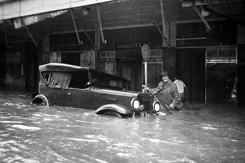 Partly submerged car outside Scarletts and Kay [Henry] stores during the Maitland Flood, 1955: Lucey Collection