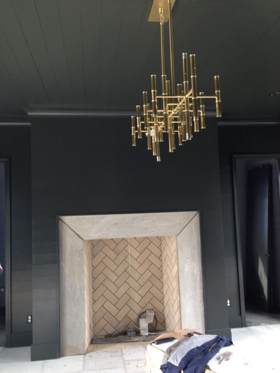 stunning dark walls, herringbone fireplace, brass chandelier-- Tracery Interiors