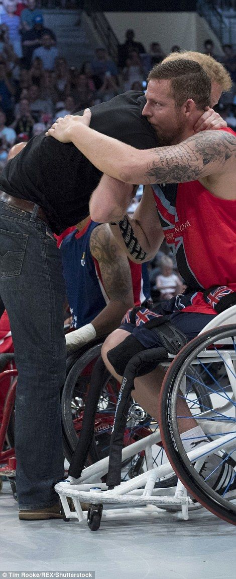 Harry hugs the  GB members of the wheelchair basketball team at the gold medal match against the USA