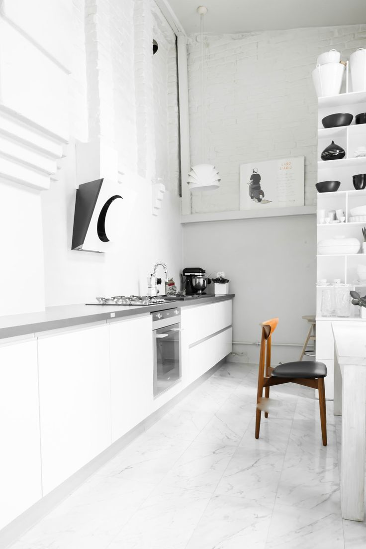 """In the kitchen, an exposed brick wall stands out against the milky smoothness of the marble tile floors. """"I wanted the house to be raw and interesting,"""" Kolasiński explains. The large cupboard was designed by his company. Appliances are by Smeg and the stove hood is by Elica."""