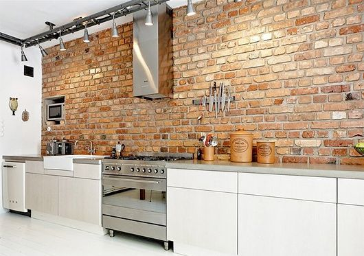 Exposed red brick kitchen wall