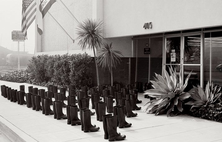 LArt De Voyager: Louis Vuittons New Four-Wheeled Suitcase And The Correspondences Exhibition. ELEANOR ANTIN 100 BOTTES À LA BANQUE / 100 BOOTS AT THE BANK, Solana Beach, California. February 9, 1971 10:00 a.m. .......................................... 100 BOOTS, 1971-73 51 photographies cartes postales noir et blanc / 51 black and white picture postcards 11,4 x 17,8 cm chaque / each Courtesy Ronald Feldman Fine Arts, New York © Eleanor Antin