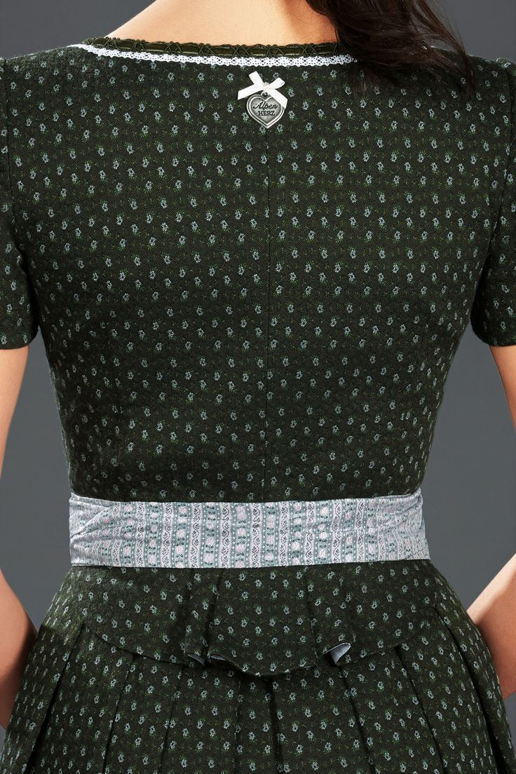 Einen einzigartigen, neuen Schnitt hat das AlpenHerz Dirndl Laura. Aus hochwertiger Jaquard-Stretchwebung gefertigt, passt es sich durch den Stretch-Anteil Ihrer Figur perfekt an. Die traditionelle Schürze in weiß-grün und die weiße Borte am Dekolltee setzen auf dem dunklen grün des Kleides Akzente. Das Dirndl besticht zudem durch das reizende Schößchen am Rückenteil und zaubert seiner Trägerin einen außergewöhnlichen und eleganten Look. Dieses Modell wird ohne Bluse getragen.