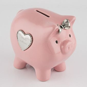 Pink Piggy Bank This sweet pink piggy bank is cute as a button! Make it even more special by engraving the recipient's name on the heart shaped metal plate.