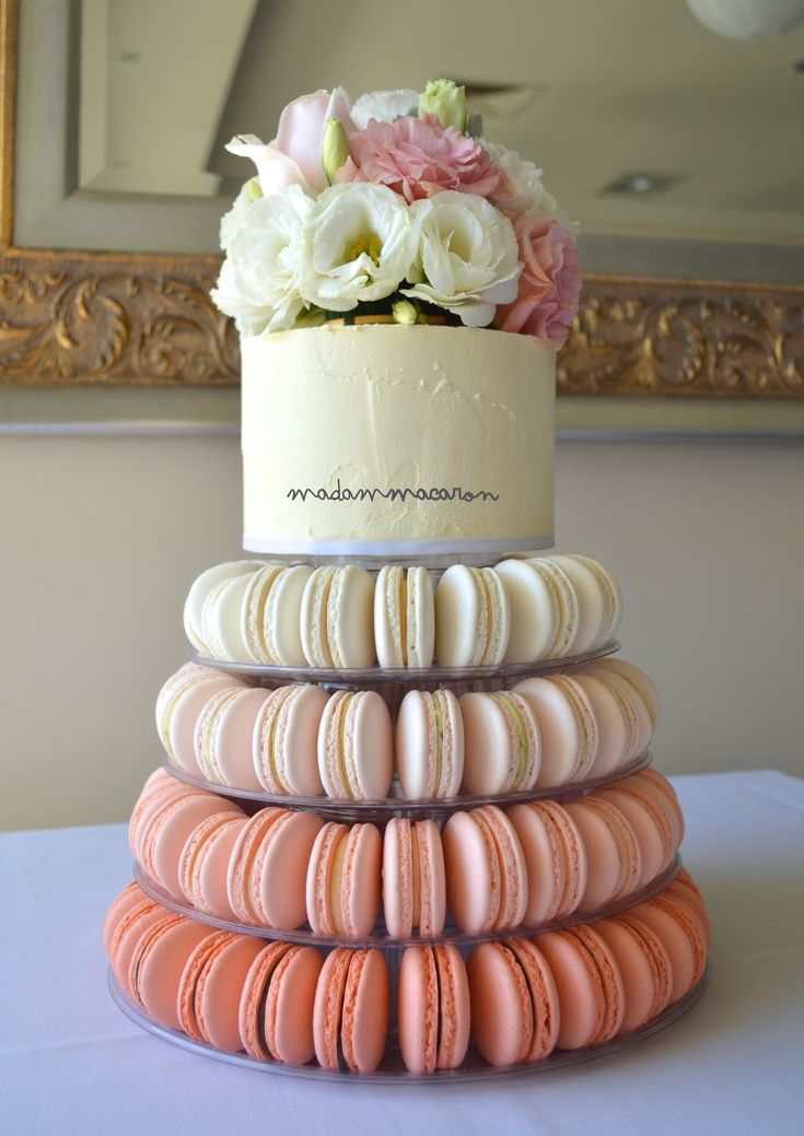 Peach Ombre macaron tower, buttercream cake on top finished with fresh flowers.