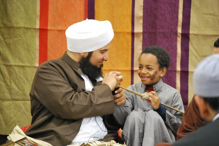 Habib Ali with a young audience member, demonstrating how the Prophet ﷺ shook hands with people