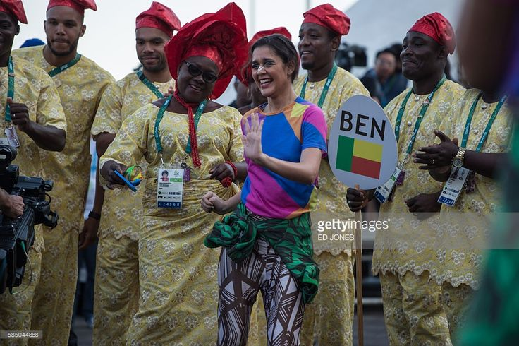 Members of the Benin Olympic team dance with performers during a welcome ceremony held at the athletes village of the Rio 2016 Olympic Games on August 1, 2016. / AFP / Ed Jones