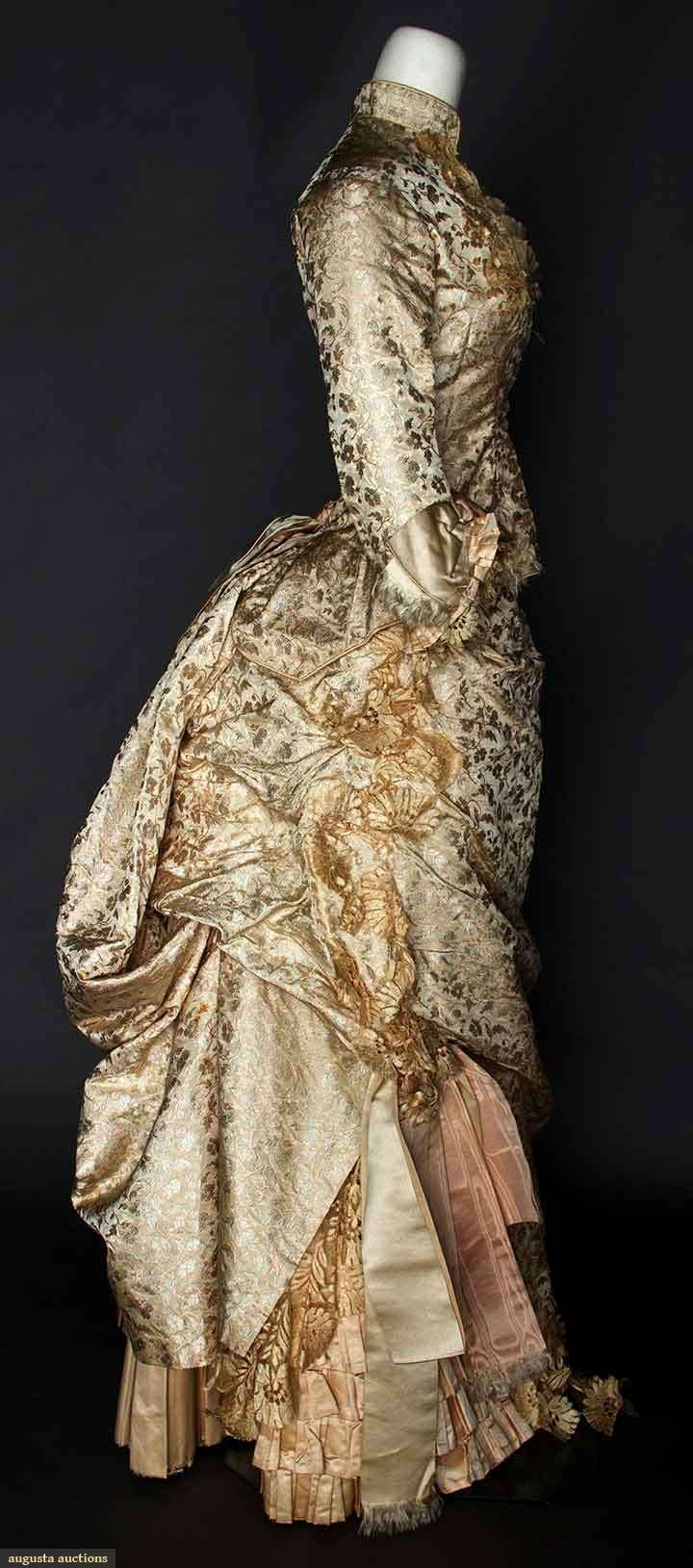 1880 SILK BROCADE WEDDING DRESS: 2-piece, pale pink brocade flowers on cream silk faille, bodice and skirt trimmed w/blonde lace, removable ruffled modesty neckpiece, cotton, satin and buckram linings.