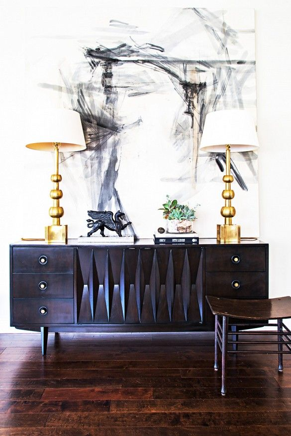 dramatic details - from the lines of the oak side board to the warm gold lamps and abstract art.: