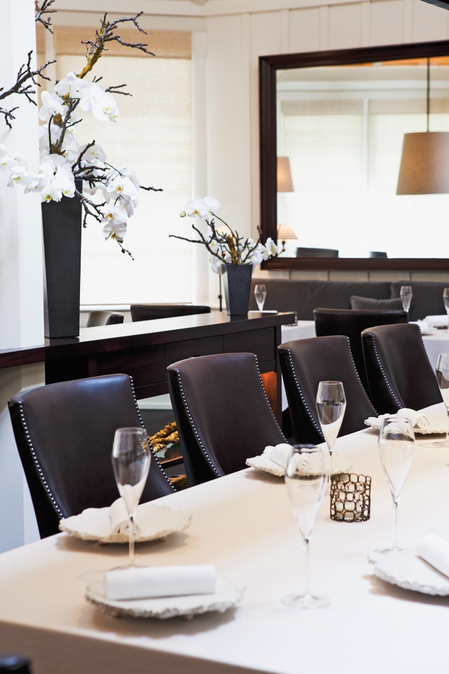 The defined lines in The Restaurant at Meadowood's serene dining room: contoured brown leather chairs, dark wood, white walls, and naturalistic blooms. - Erin Kunkel