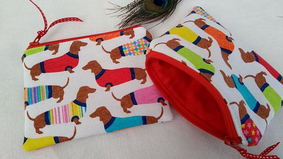 Here we have a delightful handmade coin/card purse/ small cosmetic bag, made using a quirky Dachshund print cotton by Timeless Treasures. The coin purse measures approx 12x10cm and has red cotton blend lining. Altogether this is a beautifully made item. I have more unique handmade products for sale in my shop - take a look. I love finishing touches so all my items come wrapped in my shabby chic spotty cellophane.