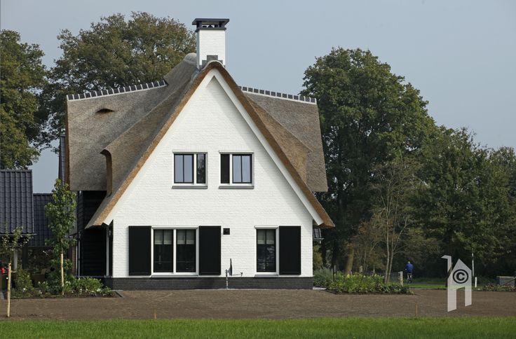 Een wit huis met een rieten kap (kameeldak) Het is een sporenkap met een gebogen nok. Heel speciaal. Het huis heeft een breed front.