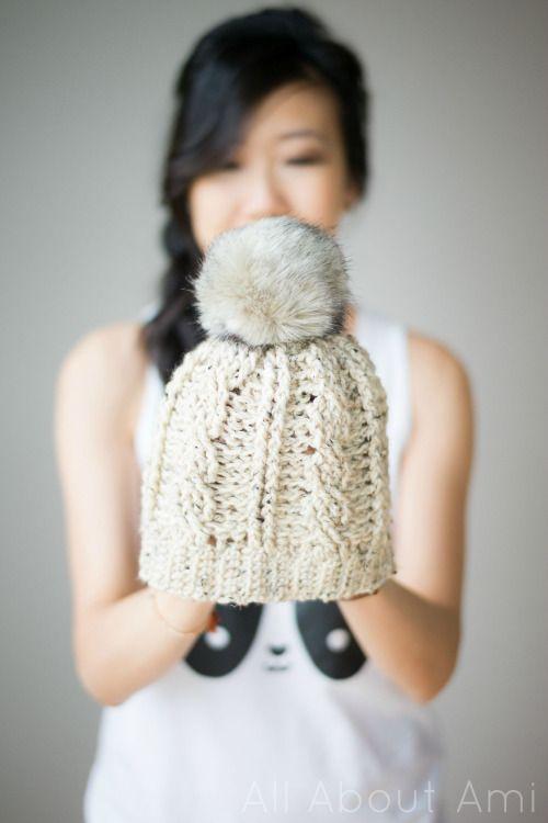 Crochet this cute cabled beanie by All About Ami! Make it with just one skein of Vanna's Choice in Oatmeal (2 makes a slouchy version) and  a 6 mm crochet hook. Top it with a faux fur pompom or make your own!: