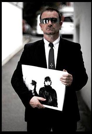 Bono, holding print of him and Anton Corbijn.