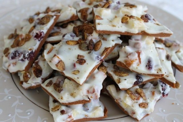 A delicious candy recipe that combines dried fruit, cranberries, nuts, and pumpkin seeds in a white chocolate and cinnamon base.