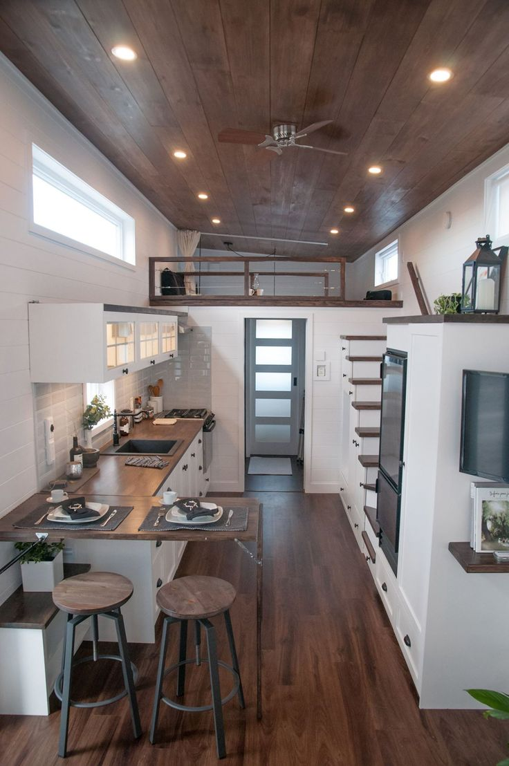 The kitchen features a wood counter, lighted cabinets, 12-volt refrigerator, two burner stove and oven, and a pull-out cabinet for trash and recycling.