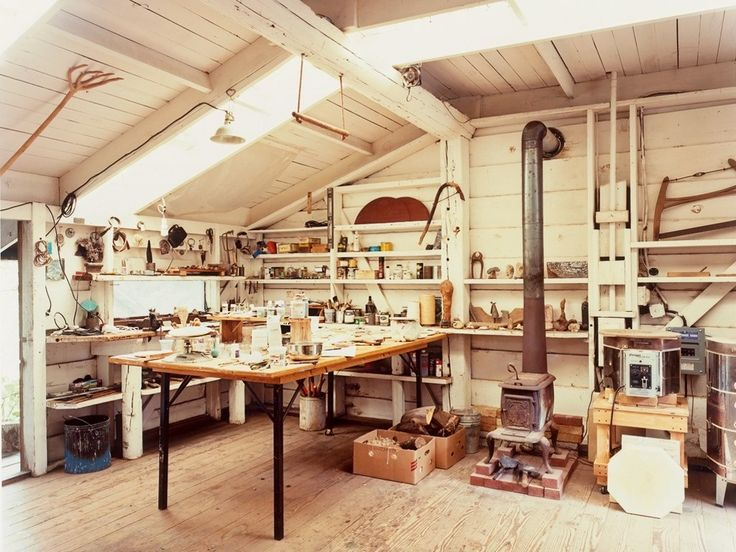 Wood sculptor JB Blunk's workspace. White painted with kiln, worktable, and woodstove.