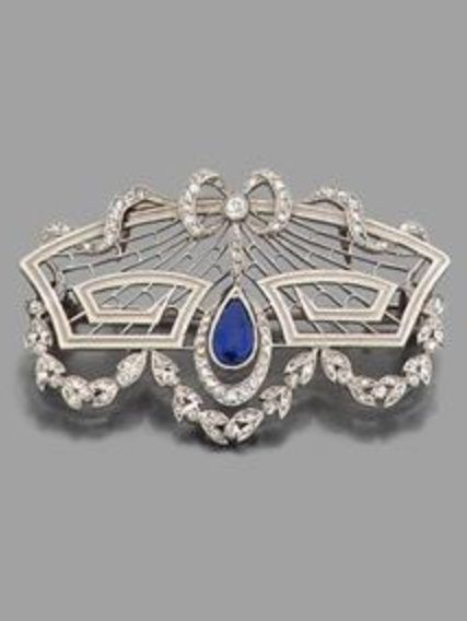 A Belle Époque gold, sapphire and diamond garland brooch, circa 1910. Openwork brooch surmounted by a diamond-set ribbon bow, centring a pear-shaped sapphire with diamond-set garlands below, mounted in white gold. #BelleEpoque #brooch