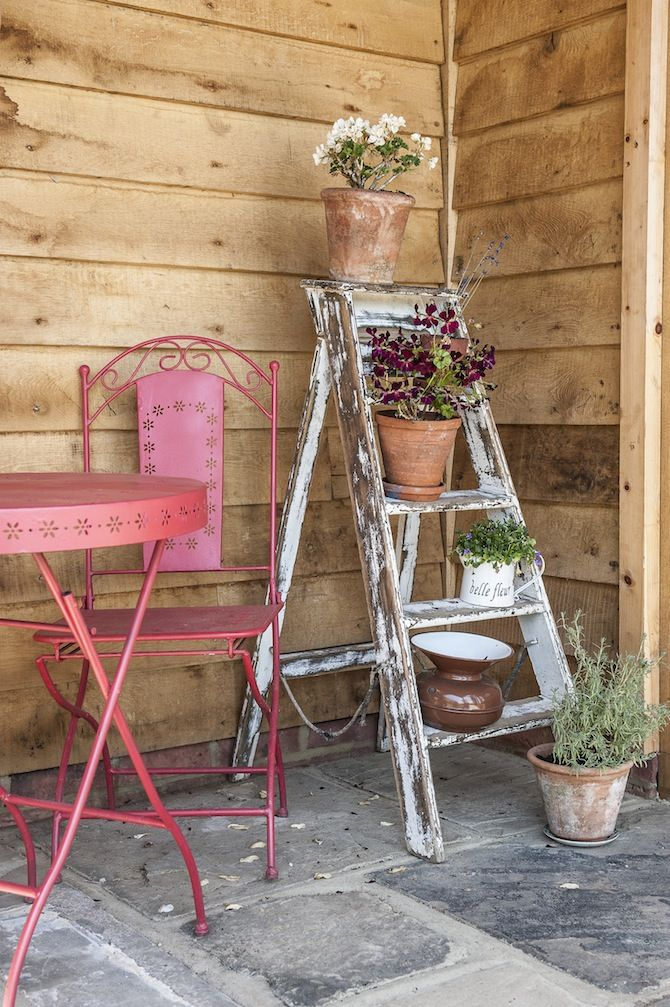 An old painted ladder used as a flower pot stand sits in ...