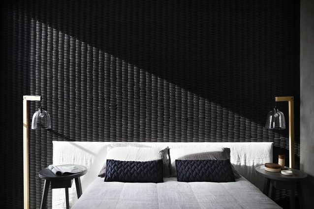 A dramatic blade wall finished in a basket weave ceramic tile slides into the main bedroom from the southern facade.