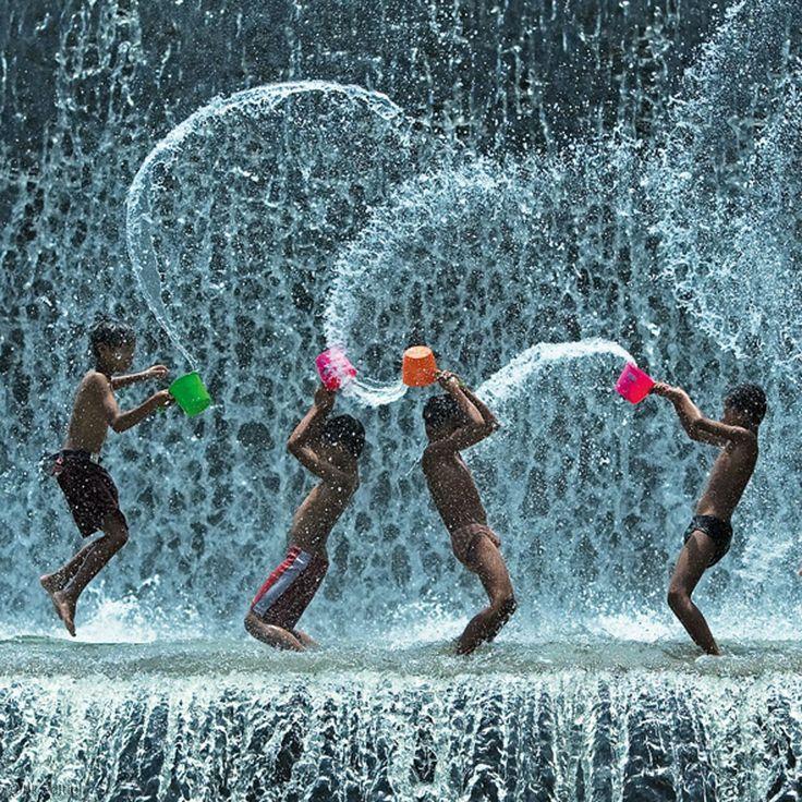 Vier Jungen fangen das kühle Nass des Wasserfalls Kali Unda auf Bali in Töpfen auf und schleudern es gegeneinander. Ein idealer Spielplatz in der tropischen Trockenzeit von Mai bis November. Dann setzt der regenreiche Nordwest-Monsun ein – Diese Karte hier online kaufen: http://bkurl.de/pkshop-212067 Art.-Nr.: 212067 Wasserspiele   Foto: © Alex Goh Chun Seong   Text: Rolf Bökemeier