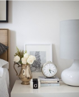 Very romantic, yet chic and not overly feminine nightstand decor.  I'm a sucker for a touch of vintage, and that pitcher turned vase is simply perfect.  Juxtaposing square and round shapes gives the white-washed vignette alot of character.  I like that it looks effortless, and not too busy.  Only the essentials, a lamp, a vessel for jewelry, a favorite book, and a clock-- the flowers and the art go along way to make it feel like home.