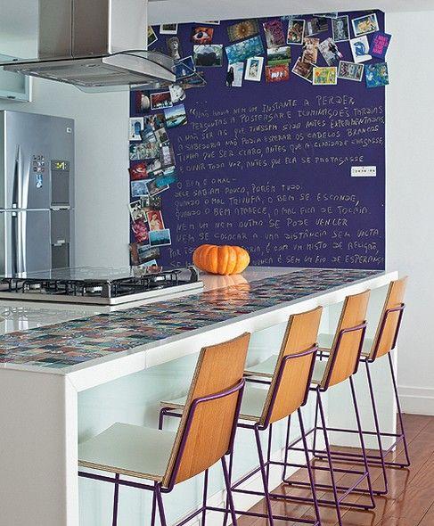 """A moradora Rosana Leal gosta de poesia e literatura. As palavras foram o mote para a reforma comandada pela arquiteta Laura Faria. """"Instalei uma chapa metálica pintada de roxo na parede da cozinha, onde ela exibe cartões-postais, fotos e textos"""", diz"""