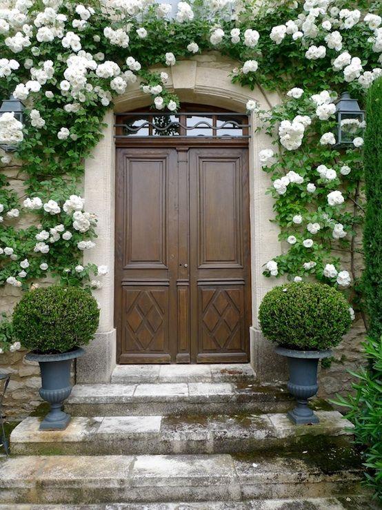 Причудливая перед входной с двери из цельного дерева, каменной мостовой и серых подстриженными урн.