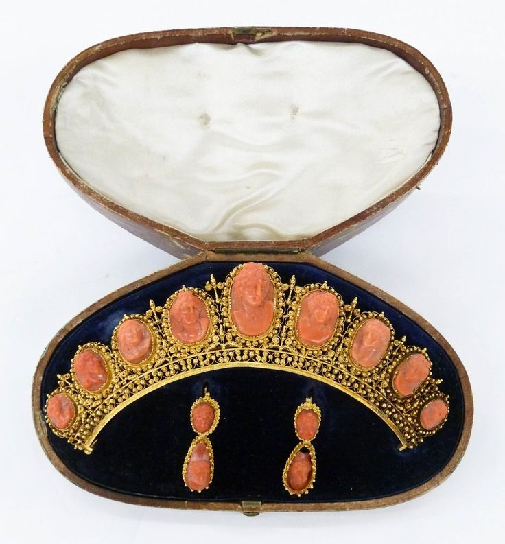 Victorian Etruscan Revival 14k Coral Cameo Jewelry Suite. Includes filigree tiara with nine relief carved coral cameos ranging in size from .5'' to 1'' in length. Also a pair of matching drop earrings 1.5''. Chip to cameo in one earring. Also finial missing to center of tiara. Comes in original velvet lined leather fitted box. Set weighing a total of 59.5 grams. Fox's Gem Shop, Seattle.