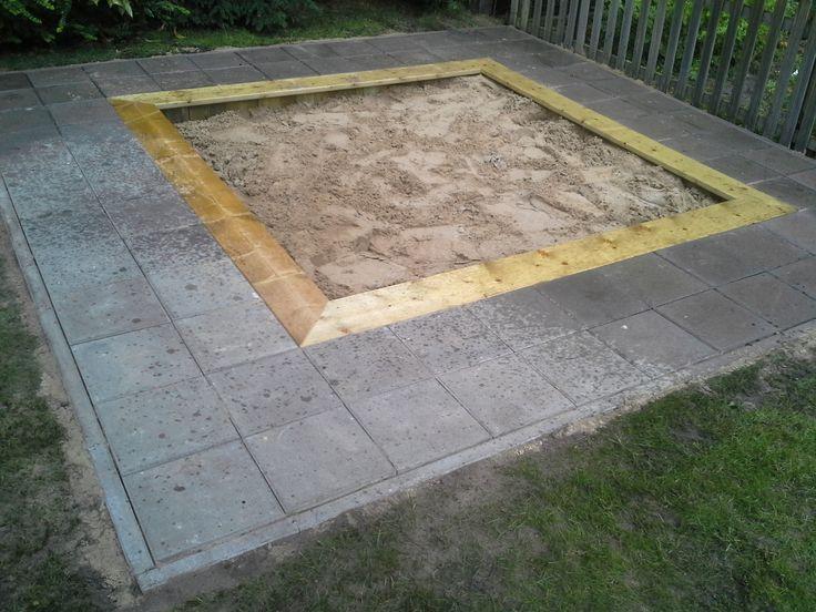 """Een zandbak met tegelrand. S'avonds na het spelen veeg je het zand zo weer in de bak en heb je het niet op het gras liggen. De brede rand is ideaal voor """"taartjes"""" bakken."""