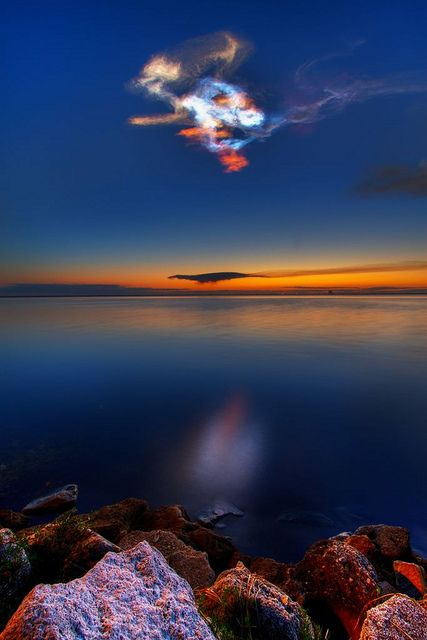 Colorful Noctilucent Clouds in the Sky, Titusville, Florida - A cloud of unknown composition which occurs at great heights and high altitudes; photometric measurements have located such clouds between 45 and 54 miles (75 and 90 kilometers); they resemble thin cirrus, but usually with a bluish or silverish color, although sometimes orange to red, standing out against a dark night sky. -