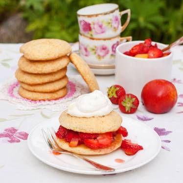 Mellan två spröda kakor  finns ett berg av jordgubbar och nektariner.