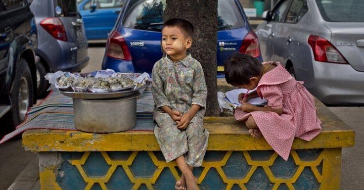20150928 - Filho de um vendedor ambulante senta ao lado de uma bandeja de ovos de codorna, enquanto sua irmã escreve em um livro de exercícios em uma calçada na cidade de Yangon, em Mianmar. De acordo com relatório do PNUD (Programa das Nações Unidas para o Desenvolvimento), uma a cada quatro pessoas vive abaixo da linha nacional de pobreza e duas a cada cinco crianças estão subnutridas. PICTURE: Gemunu Amarasinghe/AP