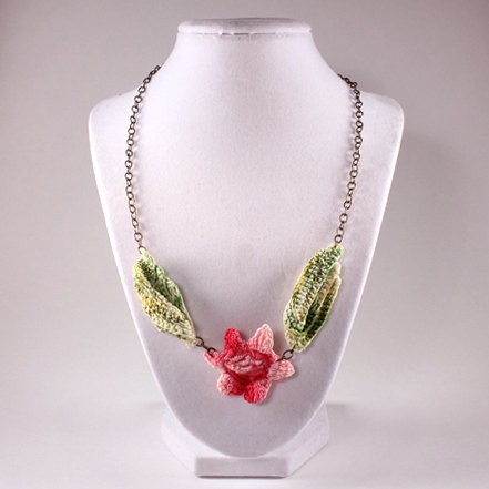 Romantic necklace features a delicate pink flower and two small green leaves from a vintage doily