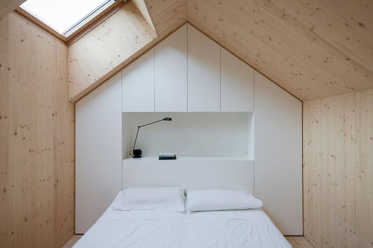 Pitched roof bedroom with skylight and wood walls. Each bedroom is designed to replicated a mini house, and follows the roof's pitch. A skylight lets in light. A custom unit made of white-painted MDF panels provides necessary storage.