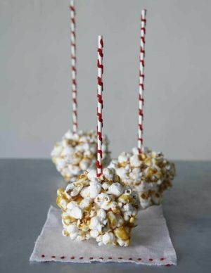 A great little snack for a kids party.  How to:  melt 1 1/2 sugar, pour over popcorn in bowl, mix, roll into balls and place on wax paper, insert stick/straw. Done!