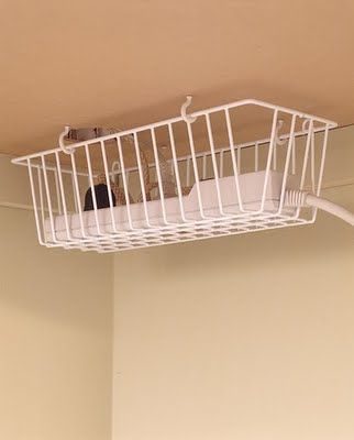 When attached to the underside of a desk, a kitchen basket is perfect for corralling cords