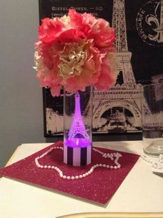 This is a cute idea - to have a glass vase witha tiny eiffel tower inside, and a flower ball on the top.