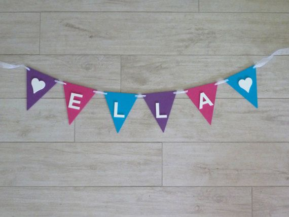 These beautiful Personalised Wooden Bunting Signs will add a special touch to your little one room. Bunting signs can also be used for back drops and photo props for birthday parties, baby shows and christenings. With over 25 colours to choose from you will be sure to find the right combination that works with your childs nursery decor.  Each bunting flag and letter is made of 3mm MDF. Flags measure 13cm wide x 15cm long. Letters are 5.5cm high. Organza ribbon is then woven through the flags…