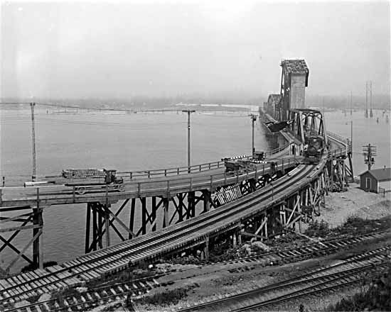 The original Second Narrows Bridge in 1926. It was designed as a lift bridge to allow both cars and trains to travel across the Burrard Inlet.