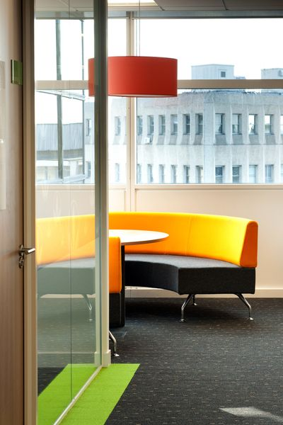 Providing touch down areas across the workplace encourages teams to work together and collaborate. This curved seating booth with central table is ideal for a quick catch up with colleagues.  Herbalife's office design encouraged colleagues to move about the floor space which keeps them healthy and promotes 'bump' meetings.   Bright colours including orange seating, green carpet and red lampshade provides a vibrant interior design.