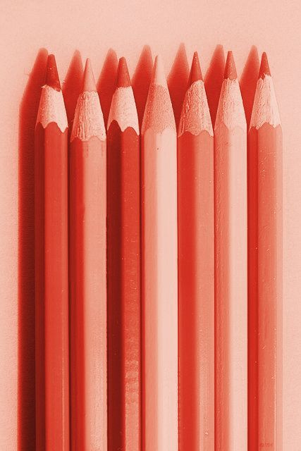 Sharpened pencils, side-by-side, in varying hues of coral. [I imagine a tinted lens or digital software was used to achieve this result.
