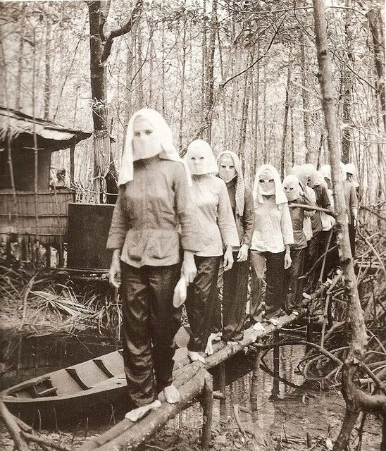"""Haunting"" Image of Viet Cong Women Fighters. Photo by Peter Alan Lloyd. It shows a group of Viet Cong women hiding their faces from the camera, having attended a training camp in the forests of South Vietnam. ~ Vietnam War"