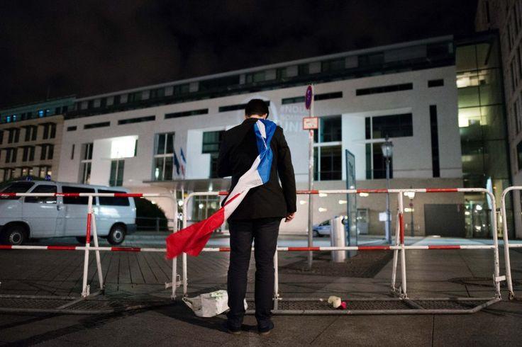 Dieser Mann hat sich eine Frankreich-Flagge um die Schultern gehängt, er steht...